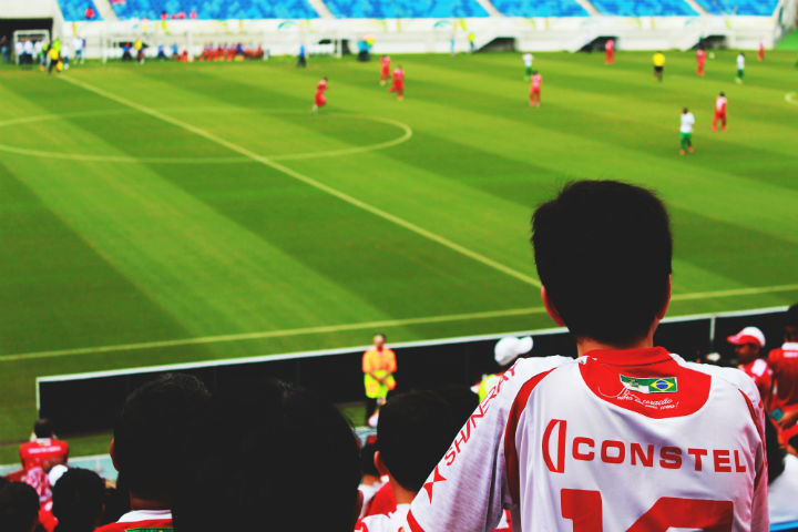 boy watching a soccer game at the stadium