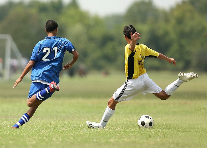 soccer player shooting with defender chasing