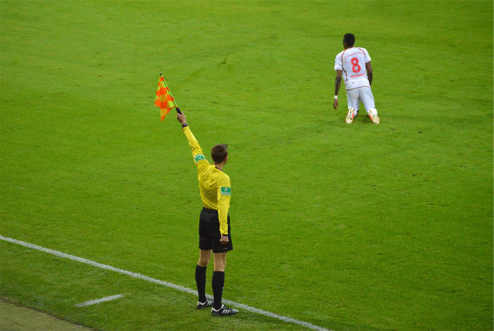 soccer assistant referee holding flag high