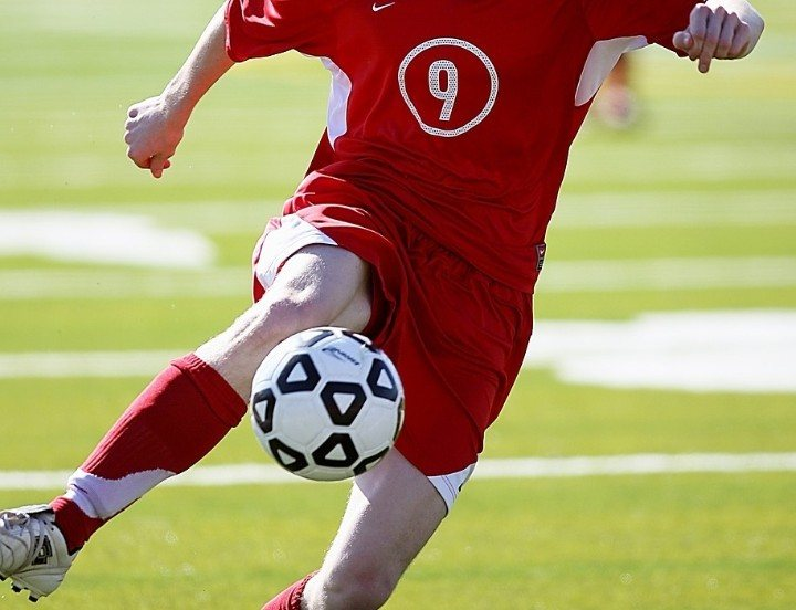 soccer player during game in red jersey with number 9