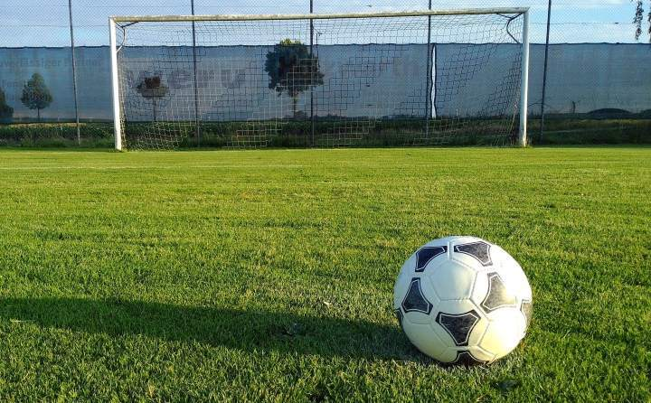 soccer goal and ball on green outdoor pitch