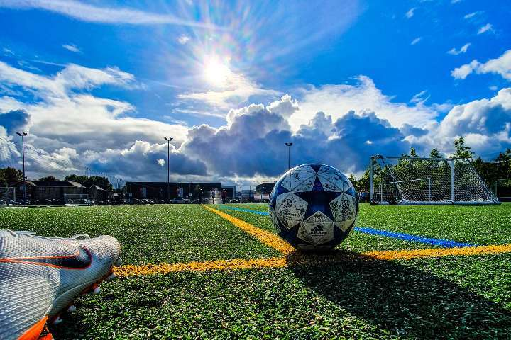 soccer ball and cleats on outdoor pitch under blue sky and sun
