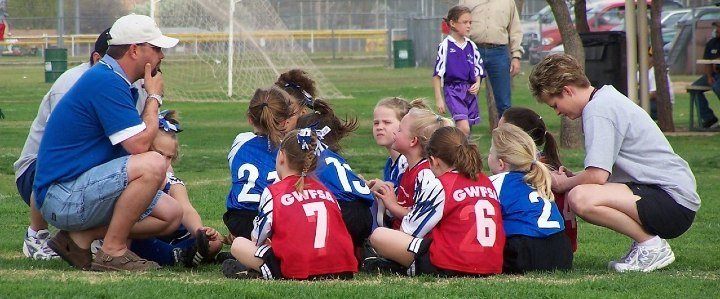 youth girls soccer team with coaches