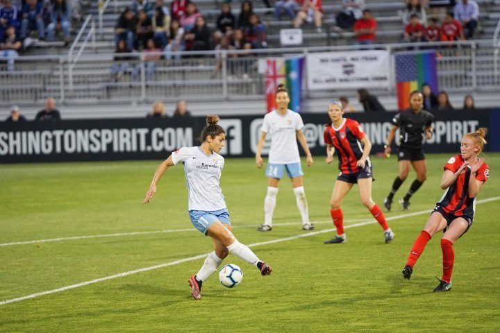 woman soccer player dribbling ball in game