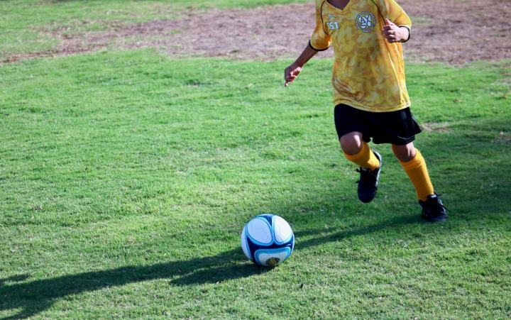 boy with a soccer ball on pitch