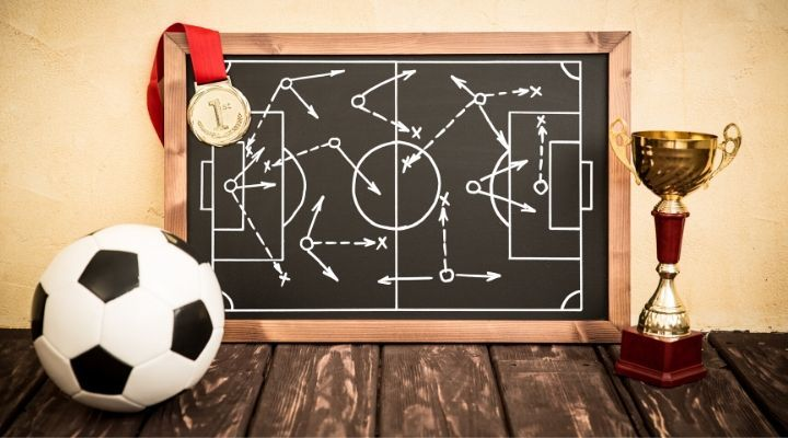 A blackboard containing a diagram of a soccer formation flanked by a soccer ball and a trophy