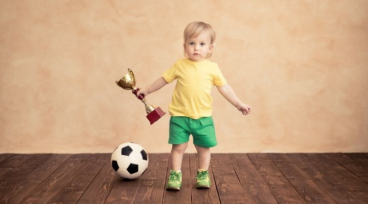 A toddler holding a trophy while a soccer ball is on the floor beside her