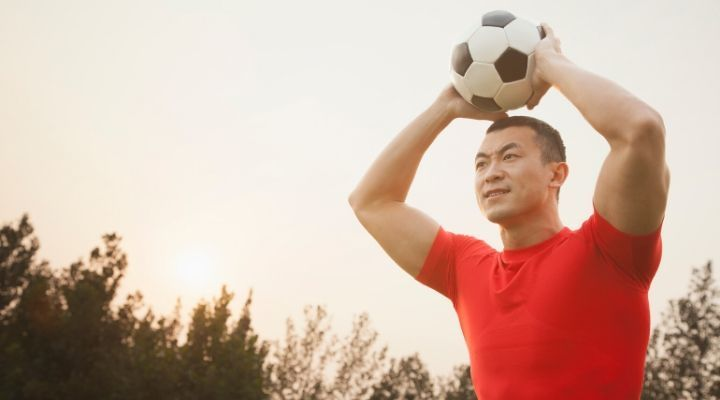 Soccer player in red shirt about to throw in the ball