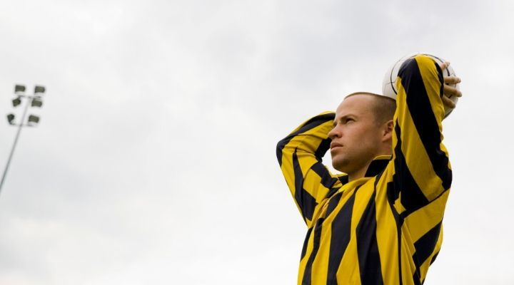 Man wearing yellow and black striped shirt holding the soccer ball above his head and about to throw the ball
