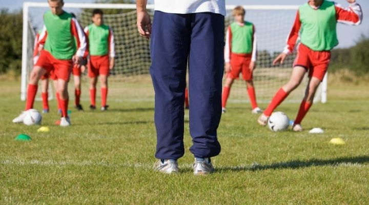 Young soccer players are lined up in front of the goal post during training while their coach explains a new drill