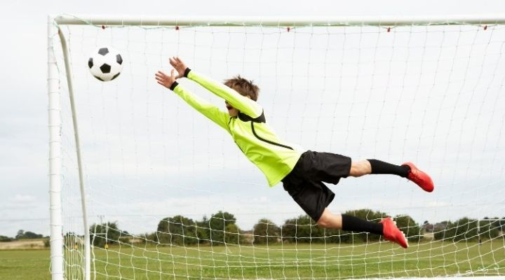 A young goalkeeper in yellow jumping to catch the ball