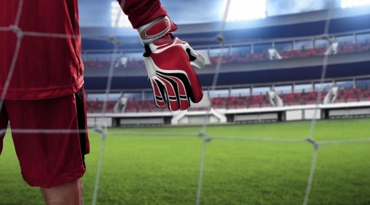 Close-up of a soccer goalkeeper's red glove with a soccer stadium in the background