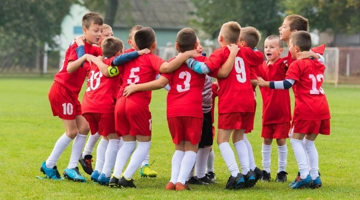 Soccer kids wearing red uniforms all gather in a huddle