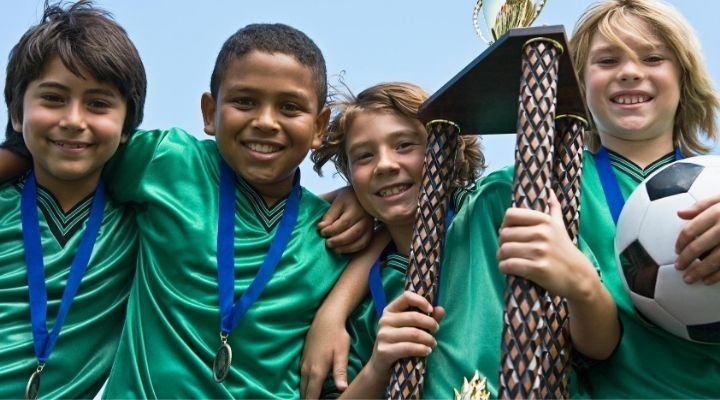 Four young soccer players smiling at the camera while showing off their medals and championship trophy