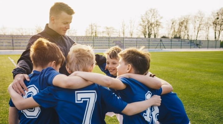 A group of young soccer players huddling in celebration with their coach