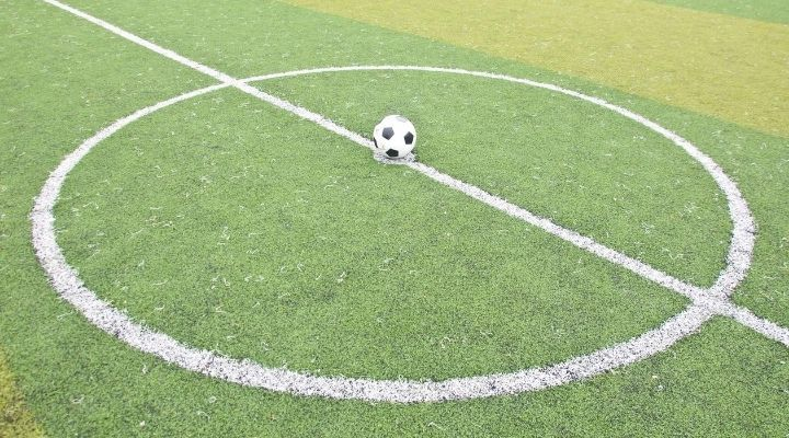 A soccer ball laying on the center of the football field