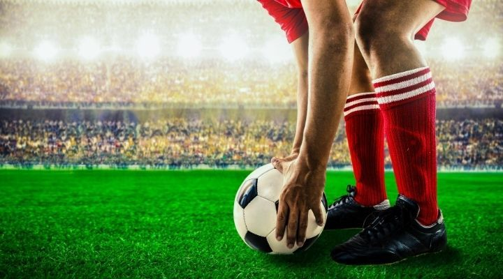 A soccer player wearing a red uniform bending down to place the soccer ball on the grass field before him