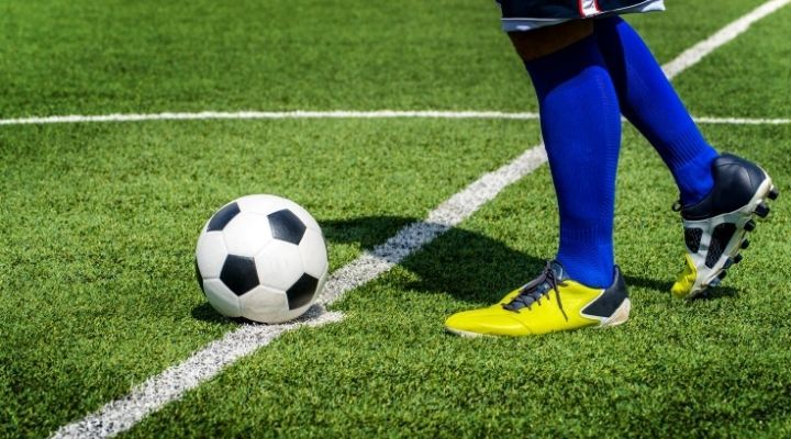 A soccer player preparing for a kick-off
