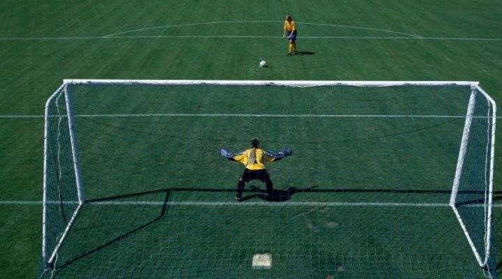 A female soccer player gets ready for a penalty kick while the goalkeeper has his arms spread wide in preparation for it
