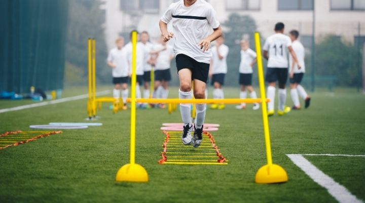 Boys doing agility training on their school's soccer pitch