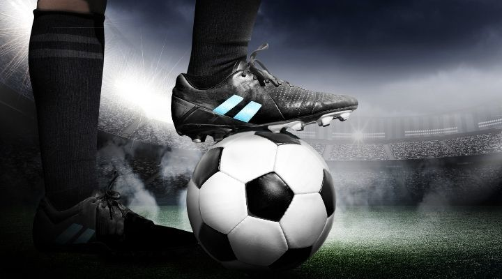 Soccer player resting his foot on the ball