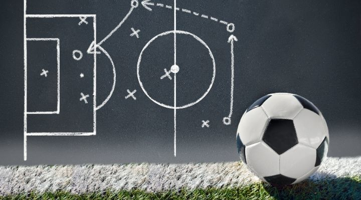 Soccer ball beside a blackboard with a strategy drawn on it with chalk