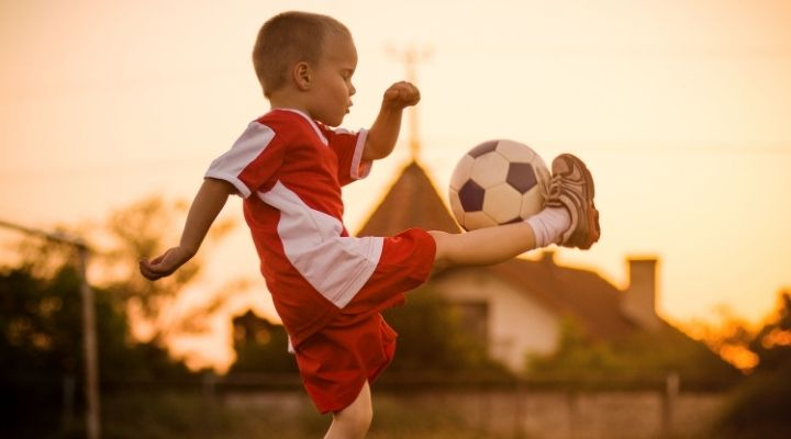 A little 4-year-old boy playing with a soccer ball outdoors