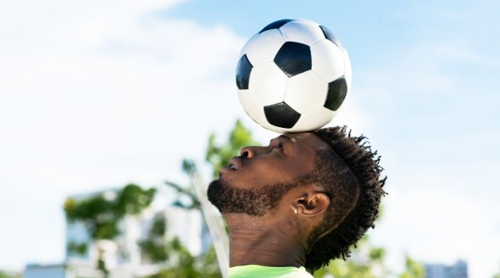 An African American soccer player balancing the ball on his head