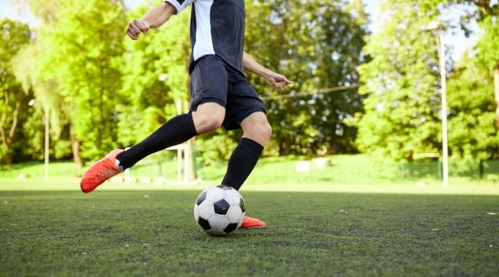 A soccer player practicing his ball control on the field
