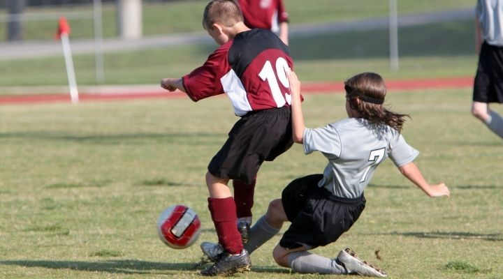 Soccer player slide tackling the opponent for the ball