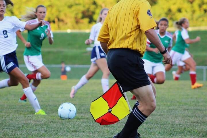 Soccer-referee-in-a-yellow-shirt-holding-a-flag
